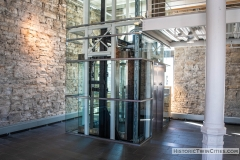 Glass elevator added during the renovation located where on of the original copper brew tanks sat