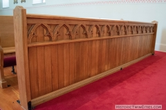 Ornate woodwork on the front row pew in the Historic Church of St. Peter in Mendota